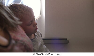 Close-up of a little boy sleeping in an airplane while flying. Slow motion.