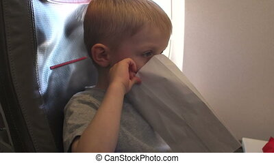 Close-up of a little boy vomits in an airplane during a flight.