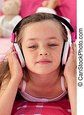 Close-up of a little girl listening music
