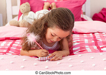 Close-up of a Little girl writing on bed