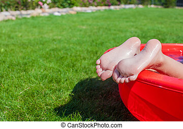 Close-up of a little girl's legs in the pool