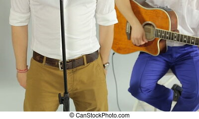 Close up of a live performance of the musical group consisting of the guys in the studio on a white background