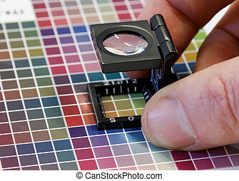 Close-up of a loupe on colorful, blurry inkjet test print with color dark shades in cyan, blue, magenta, red, green, orange, and yellow. Short DOF