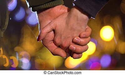 Close-up of a loving couple holding hands in winter