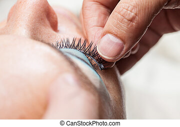 Close up of a makeup artist applying the false eyelashes to a woman