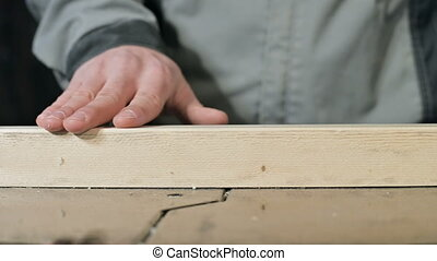 Close-up of a male carpenter's hand checking the smoothness...