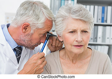 Close-up of a male doctor examining senior patient's ear