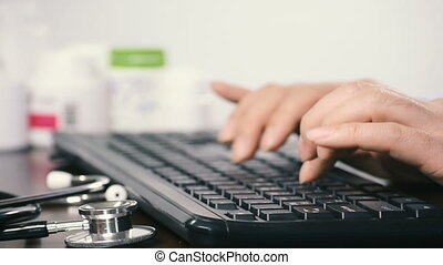 Close-up of a male doctor using a computer keyboard.