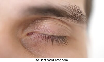 Close up of a male eye. Detail of opening brown a eye of a...