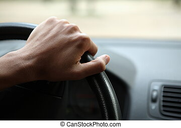 Close-up of a male hand on steering wheel in a modern car
