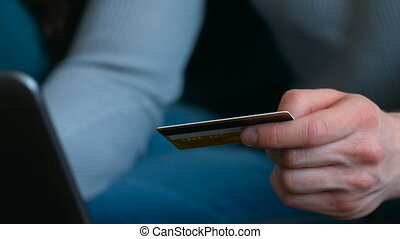 Close up of a male hands holding gold card and making shopping in internet.