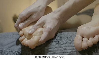 Close up of a male hands massaging the toes and the foot of...