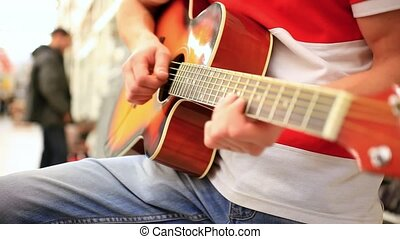 Close up of a male musician in jeans playing acoustic guitar.