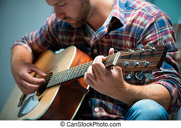 musician playing acoustic guitar - close up of a male ...