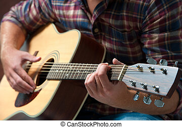musician playing acoustic guitar - close up of a male...