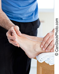 Close-up of a male physical therapist giving a foot massage