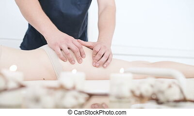 Close-up of a male physiotherapist doing a light massage to...