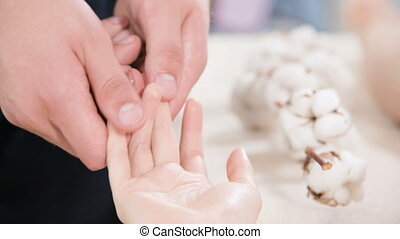 Close-up of a male physiotherapist doing finger and palm...