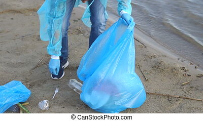 Close-up of a male volunteer collecting plastic garbage from a river or lake.