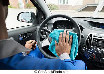 Worker Cleaning Car Steering Wheel