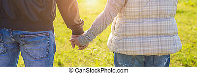 Close up of a man and a woman holding hands outdoor