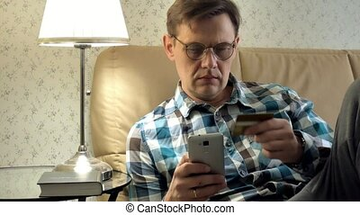 Close-up of a man buying online uses a phone and a credit...