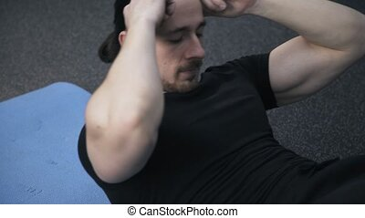 Close up of a man doing crunches in a gym