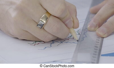 Close-up of a man drawing a line on a ruler on the chart....