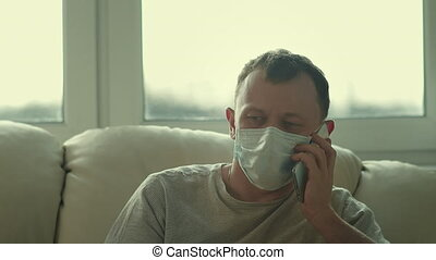 Close-up of a man in a medical mask sitting on a sofa and talking on the phone