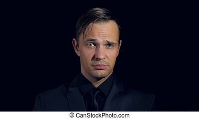 close-up of a man in black clothes on a black background. 4k. Slow motion. man touches his neck guilty, guiltily smiles and looks at the camera