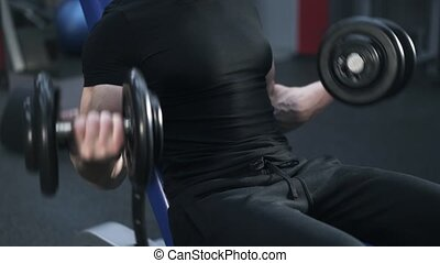 Close up of a man in black doing a dumbbell exercise in gym
