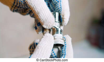 Close up of A man is sealing tape wrap around iron water tap screw