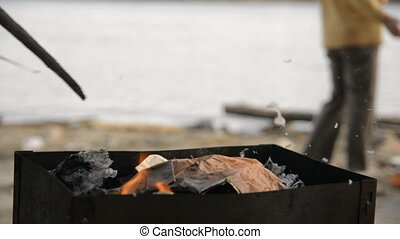 Close-up of a man is stirring a burning coal in a brazier....