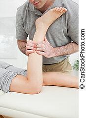 Close-up of a man massaging the leg of a woman