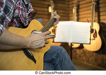 Close up of a man playing acoustic guitar.