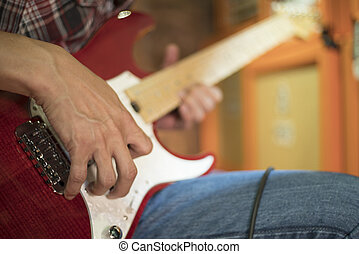 Close up of a man playing electric guitar.