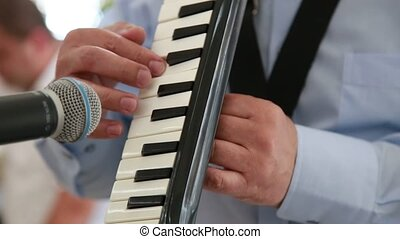 Close-up of a man playing on the musical instrument MELODICA