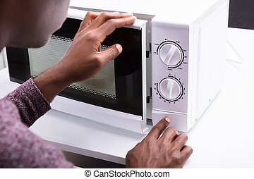 Man Pressing Button Of Microwave Oven