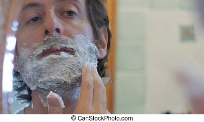 Close up of a man putting on shaving cream on a full beard -...