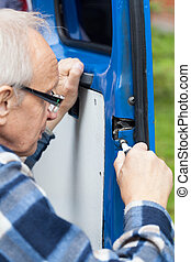 Close-up of a man repairing car door