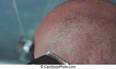 Close up of a caucasian bald man shaving his head with electric razor.