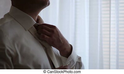 close-up of a man straightens his tie