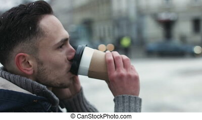 Close-up of a man talking on cellphone outdoors on winter day. Young male have a sweet conversation on telephone while waiting for a date and sipping coffee to go.