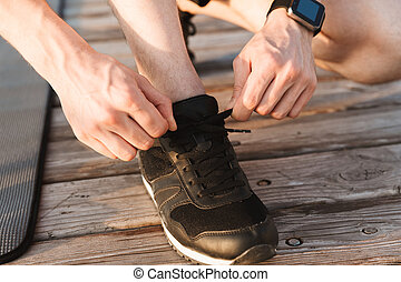 Close up of a man tying his shoelaces on the wooden