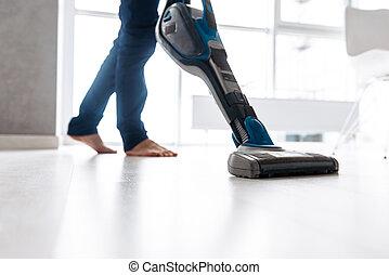 Close up of a man vacuuming