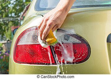 Close-Up of a man washing his car.