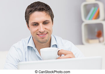 Close-up of a man with teacup using laptop at home