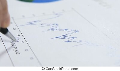 Close up of a man writing on a graph