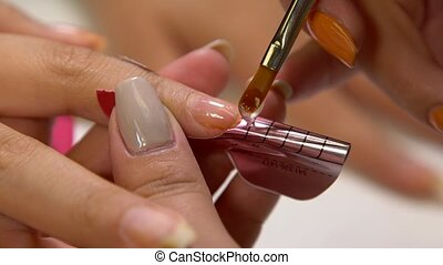 Close up of a manicurist filing woman's nails in the salon.