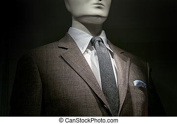 Close-up of a mannequin in a brown checkered jacket with...